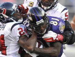 Ravens wide receiver Anquan Boldin (81) tries to shake off Houston Texans defenders Johnathan Joseph (24) and DeMeco Ryans during the second half in  Baltimore.