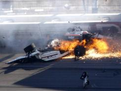 Dan Wheldon, front, and Will Power crash during a wreck that involved 15 cars during the IndyCar Series race. Wheldon was killed in the accident.