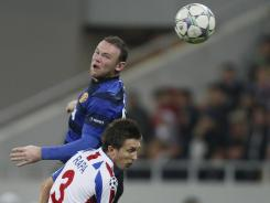 Manchester United's Wayne Rooney (top) jumps for a header with Otelul Galati's Cornel Rapa during their Group C Champions League match on Tuesday.