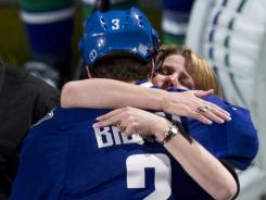 Canucks defenseman Kevin Bieksa, Rick Rypien's best friend, hugs Rypien's mother, Shelly, before Vancouver's game against the New York Rangers.