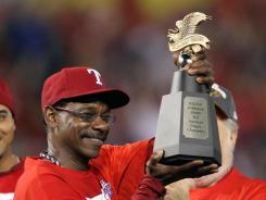 Rangers manager Ron Washington hoists the American League championship trophy after his team defeated the Detroit Tigers in Game 6.