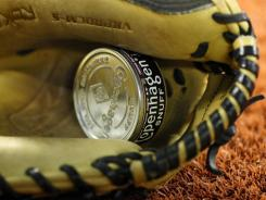 A tin can of chewing tobacco rests in a glove before the Major League game.