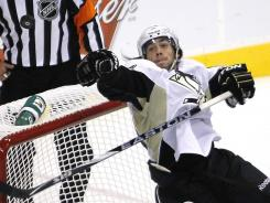 Pittsburgh defenseman Kris Letang bats away a loose puck from the Penguins' crease during Monday's game.