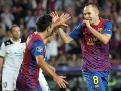 Andres Iniesta, right, celebrates with teammate Xavi after scoring in the 10th minute of Barcelona's 2-0 win. The defending champions are tied with AC Milan for the Group H lead after three matches.