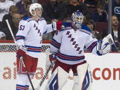Rangers goalie Henrik Lundqvist, right, gets congratulated by teammate Tim Erixon after shutting out the  Canucks on Tuesday. Lundqvist made 40 saves in the win.