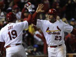 David Freese, right,  celebrates with Jon Jay after Freese scored in the sixth inning on Allen Craig's RBI single.