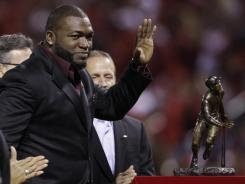 David Ortiz stands next to the Roberto Clemente Award on Thursday night at Busch Stadium in St. Louis. The award is given yearly to a player who gives back through community service and also excels on the field.