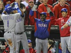 The Rangers' Elvis Andrus, left, and manager Ron Washington, right, surround DH Michael Young, whose sacrifice fly scored Andrus with the go-ahead run in the ninth inning.