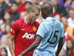Manchester United defender Nemanja Vidic, left, and Manchester City forward Mario Balotelli have a heated exchange during the FA Community Shield in August, the last time the two clubs met. City currently holds a two-point lead over United in the Premier League standings.
