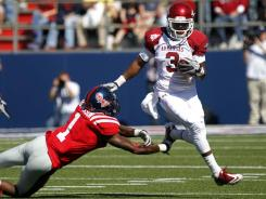 Arkansas wide receiver Joe Adams leaps past an attempted tackle by Mississippi safety Damien Jackson during the first half.