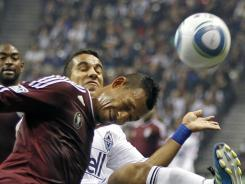 Colorado Rapids midfielder Tyrone Marshall runs through a challenge from the Vancouvers Whitecaps' Camilo Sanvezzo.