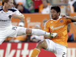 Houston Dynamo forward Brian Ching gets caught by the Los Angeles Galaxy's Dan Keat at Robertson Stadium in Houston.