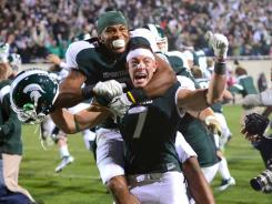B.J. Cunningham (3) and Keith Nichol (7) of the Michigan State Spartans celebrate Nichol catching a game-winning 44 yard touchdown pass from Kirk Cousins as time ran out to defeat the Wisconsin Badgers 37-31 at Spartan Stadium on October 22, 2011.