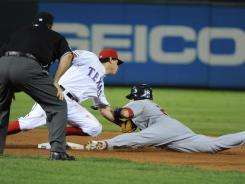 The Cardinals' Allen Craig is caught stealing to complete a ninth-inning double play as the Rangers' Ian Kinsler makes the tag,