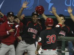 Canada's Chris Robinson (30) high fives with teammates after scoring in the sixth inning of the Pan Am Games baseball final against the U.S. Canada won the gold medal game 2-1.