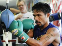 Manny Pacquiao works out as trainer Freddie Roach looks on at the Wild Card Boxing Club in Los Angeles.