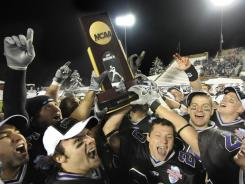 Wisconsin-Whitewater players celebrate with the championship trophy after winning the 2009 Stagg Bowl against Mount Union.