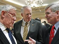 NCAA President Mark Emmert, right, talks with Northwestern University President Emeritus Henry Bienen, left, and Knight Commission co-chair Brit Kirwan, chancellor of the University of Maryland.