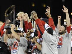 Lance Berkman holds up the trophy as the Cardinals celebrate their World Series title after defeating the Rangers in Game 7.