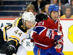 Dennis Seidenberg, left, of the Bruins strips the puck from the Canadiens' Brian Gionta during their game at the Bell Centre in Montreal on Saturday.