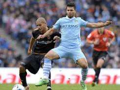 Manchester City striker Sergio Aguero, right, vies with Wolverhampton Wanderers midfielder Adlene Guedioura. City won 3-1 to stay clear at the top of the table.