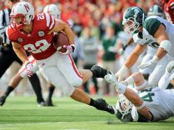 Nebraska running back Rex Burkhead tries to break a tackle against the Michigan State defense.