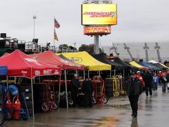Crewmembers walk in the garage area Saturday as rain falls prior to the scheduled Sprint Cup practice.