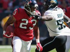 Jacksonville linebacker Clint Session grabs Houston Texans running back Arian Foster's facemask while attempting to tackle him Sunday. Foster finished with 112 yards rushing.