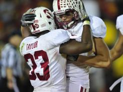 Stanford's Stepfan Taylor (#33) celebrates his TD in the third overtime with teammate Coby Fleener at the Los Angeles Memorial Coliseum. Stanford won 56-48.
