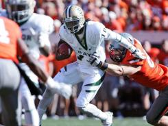 Quarterback Robert Griffin III of the Baylor Bears is grabbed by defensive end Cooper Bassett of the Oklahoma State Cowboys in the first half October 29, 2011 at Boone Pickens Stadium in Stillwater, Oklahoma. Oklahoma State defeated Baylor 59-24.