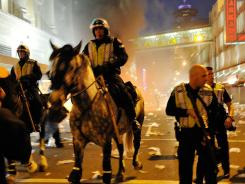 Police on horseback ride through the streets of Vancouver past a fire during riots following Game 7 of the Stanley Cup on June 15.