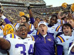 LSU Tigers running back Stevan Ridley (34) and head coach Les Miles sing the school alma mater after LSU defeated Alabama 24-21 in 2010.