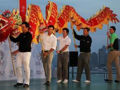 Francesco Molinari of Italy, Adam Scott of Australia, Rory McIlroy of Northern Ireland, Lee Westwood of England and Keegan Bradley of the USA take part in a traditional Chinese Dragon dance.