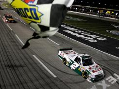 Kevin Harvick takes the checkered flag at the NASCAR Camping World Truck Series WinStar World Casino 350k at Texas Motor Speedway on Friday.