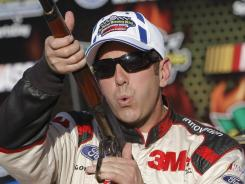 Greg Biffle gets the customary rifle given out to the pole winner at Texas Motor Speedway's races.