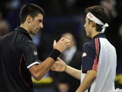 Serbia's Novak Djokovic, left, shakes hands with Japan's Kei Nishikori, right, after losing in the semifinals at the Swiss Indoors tournament in Basel, Switzerland on Saturday.