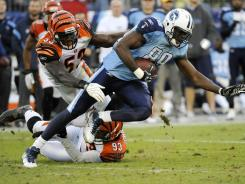 Titans tight end Jared Cook is tripped up by Bengals linebacker Thomas Howard (53) and defensive end Michael Johnson (93).