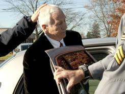 Police put former Penn State football assistant Jerry Sandusky into a car Saturday on his way to his arraignment.