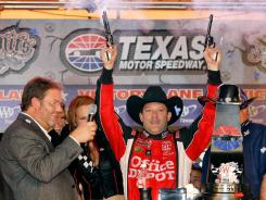 Tony Stewart celebrates with the obligatory guns-a-blazing at Texas Motor Speedway after dominating for his fourth Chase win.