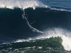 Big wave surfer Garrett McNamara, 44, of Hawaii, rides what is being called the tallest wave ever surfed in Portugal on Nov. 1.