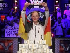 Pius Heinz, 22, holds up the winners' bracelet after grabbing a victory in the World Series of Poker main event. In front of him sits the $8.72 million in cash he takes home for winning the tournament.