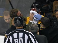 Trainers tend to Boston Bruins left wing Daniel Paille after he was injured during the third period against the New York Islanders.