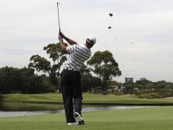 Tiger Woods plays a shot across a water hazard on the 14th hole during a pro-am Wednesday for the Australian Open.