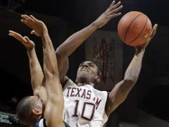 Texas A&M's David Loubeau (10) shoots over Liberty's David Minaya (14) during the first half of their season opener in College Station, Texas. Loubeau was one of three Aggies in double figures in an 81-59 victory.
