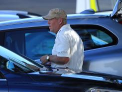 John Daly prepares to leave the course in a car after walking off in a rage during the 11th hole of the Australian Open's first round.