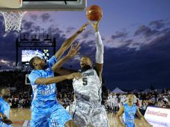 Michigan State's Adreian Payne (5) shoots over Norh Carolina's John Henson (31) during the Carrier Classic aboard the USS Carl Vinson.