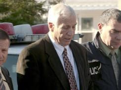 Jerry Sandusky, center, is escorted by Pennsylvania State Police and Attorney General's Office officials on Nov. 5.