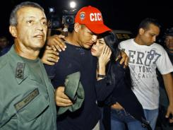 Nationals' catcher Wilson Ramos is greeted by an unidentified friend at the Criminal Police ( CICPC ) headquarters in Valencia,