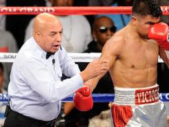 Joe Cortez, left, was the referee for Floyd Mayweather's controversial September win over Victor Ortiz, right. Cortez had hoped it would be his last bout before retirement.