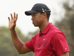 Tiger Woods acknowledges the crowd after putting for birdie on the third hole during day four of the Australian Open .